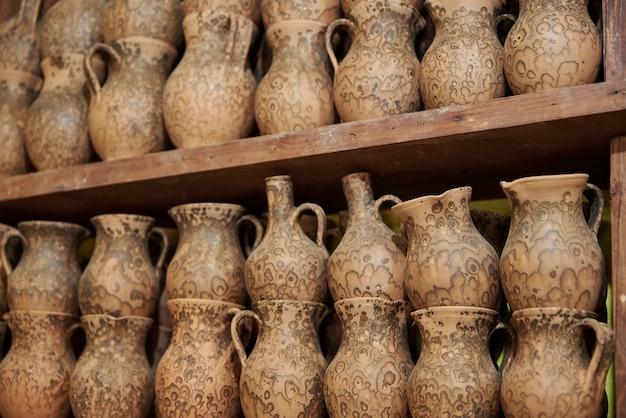 ワークショップの棚に手作りの粘土の水差し Premium写真