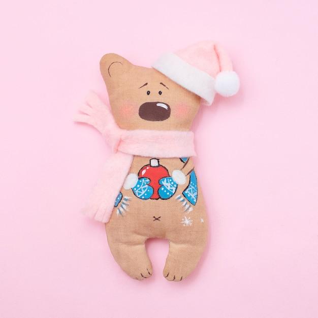 Handmade cute teddy bear santa on pink background Premium Photo