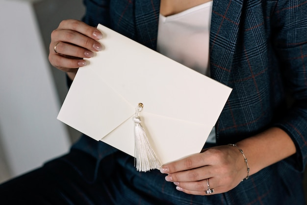Handmade gift envelope in female hands. holiday packaging. wedding invitations. Premium Photo