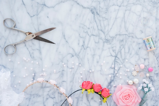 Handmade hairband with beads; rose flower; spool and scissor on marble textured backdrop Free Photo