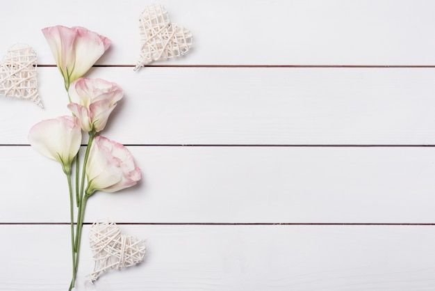 Handmade heart shape with pink eustoma flowers on white wooden desk Free Photo