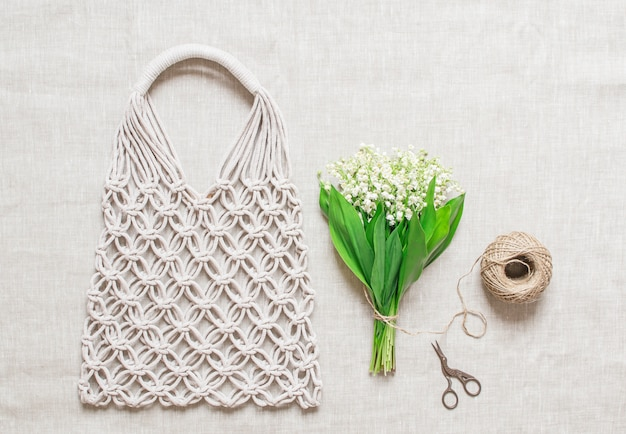 Handmade macrame bag on linen background Premium Photo