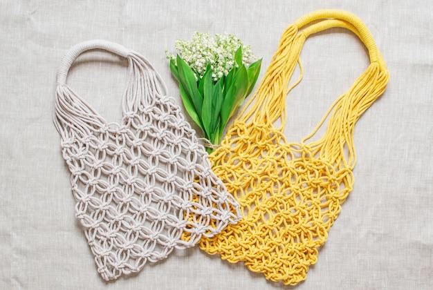 Handmade macrame bag on linen background Premium Photo
