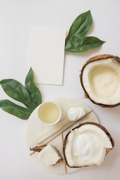 Handmade natural body scrub made with coconut and blank card on white backdrop Free Photo