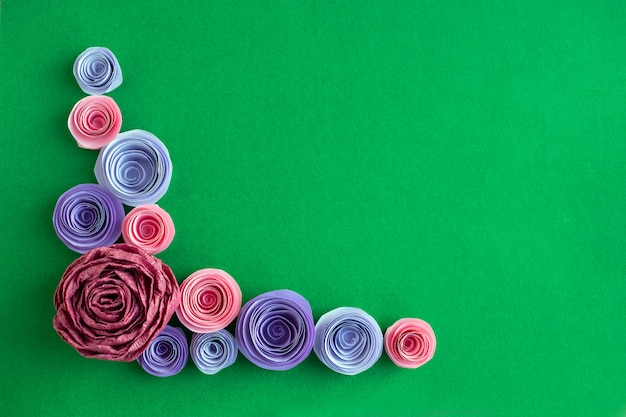 Handmade paper flowers angled frame on a green background Premium Photo