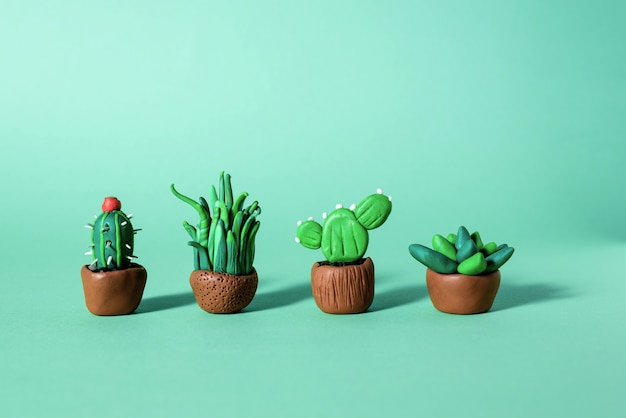 Handmade plasticine green cactuses and succulents in a pots. Premium Photo