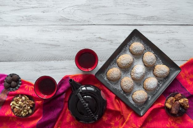 手作りのラマダンのお菓子には、背景にお茶が添えられています。エジプトのクッキー「カフエルイード」-エルフィットイスラムf宴背景のクッキー Premium写真
