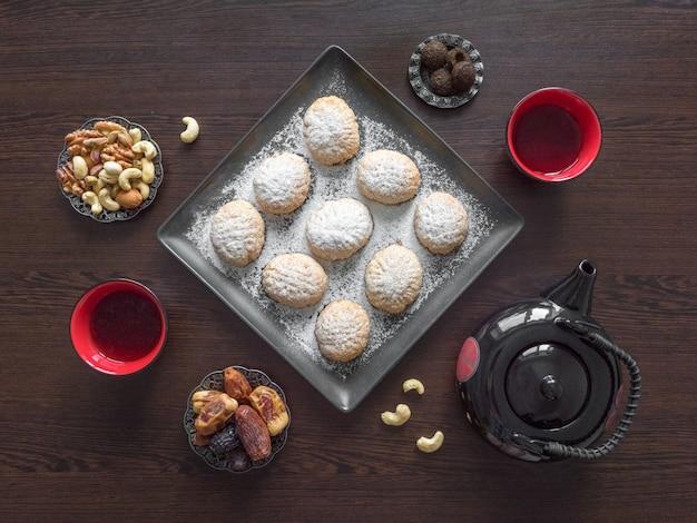 手作りのラマダンのお菓子は、暗い木製のテーブルでお茶と一緒にお召し上がりいただけます。エジプトのクッキー「カフエルイード」-エルフィトルイスラムのeast宴のクッキー。上面図 Premium写真