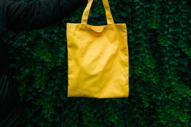 Handmade shopping bag on green plant background. blank canvas bag, design mockup with hand. Premium Photo