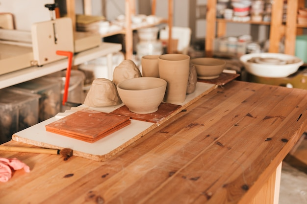 Handmade tiles and clay tableware on wooden table in the workshop Free Photo