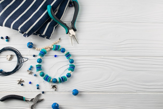 Handmade turqouise bracelet, overhead flat lay composition with plier, beads and tools Premium Photo