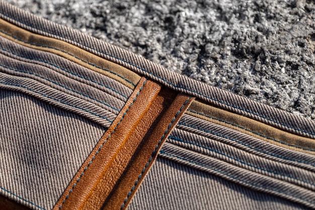 Кошелек ручной работы из коричневой кожи и клетчатой ткани на камне Premium Фотографии
