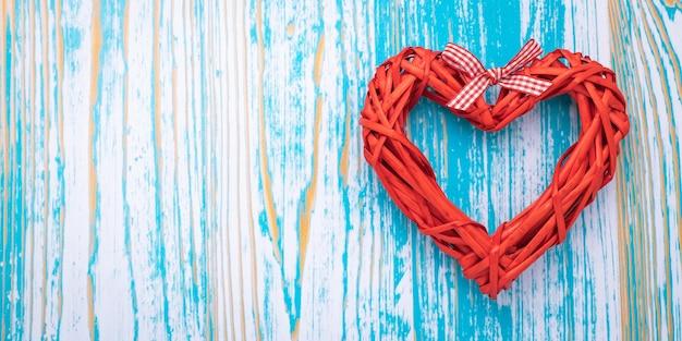 Красное handmade сердце на голубой деревянной предпосылке, шаблоне с космосом экземпляра. романтическая открытка в винтажном стиле и лаконичный дизайн. день святого валентина - праздник. Premium Фотографии