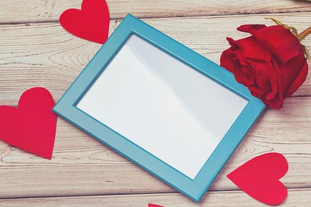 Рамка для фотографий дня святого валентина или поздравительная открытка и handmaded сердца по столу. вид сверху с copyspace Premium Фотографии