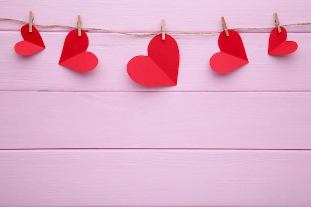 Handmaded сердца на веревке на розовом фоне. Premium Фотографии