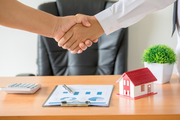 Hands of agent and client shaking hands after signed contract buy new apartment. Free Photo
