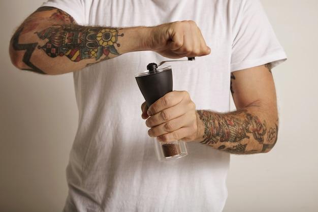 Руки и грудь молодого человека с татуировками, измельчающего кофе в ручной кофемолке Бесплатные Фотографии