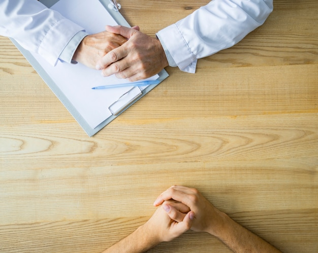 Hands of anonymous doctor and patient on table Free Photo