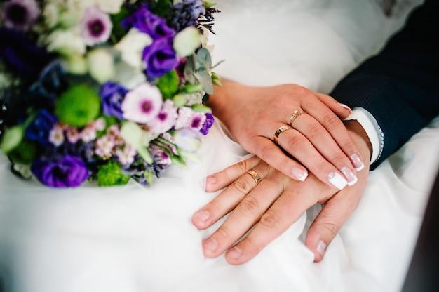 손은 결혼 반지를 가진 신혼 부부입니다. 확대. 꽃의 웨딩 부케의 배경. 신부 매니큐어. 신랑 프리미엄 사진