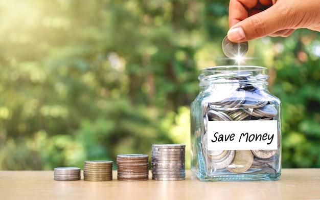 Premium Photo Hands Are Putting Money In A Jar Of Money Money Saving Ideas