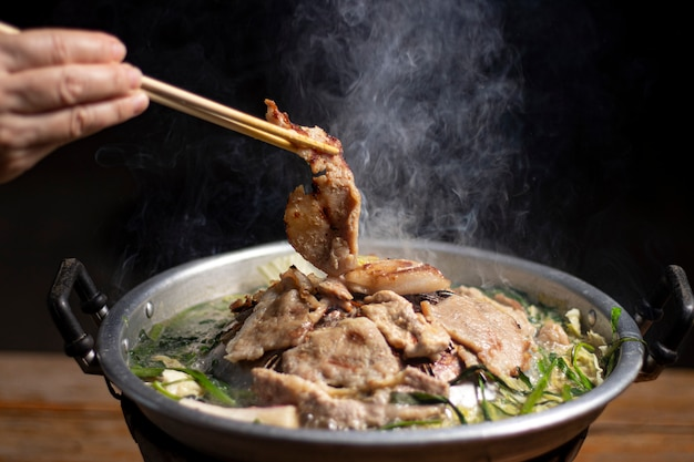 Premium Photo | Hands are using chopsticks to thai barbecue buffet with  smoke.