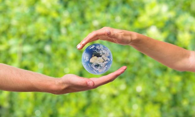 Руки вокруг земной миниатюры Premium Фотографии