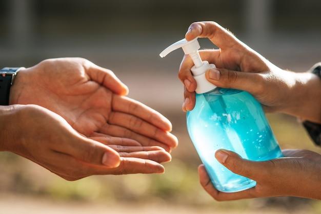 手を洗うためにジェルボトルに手をかけ、他の人が手を洗うために絞る。 無料写真