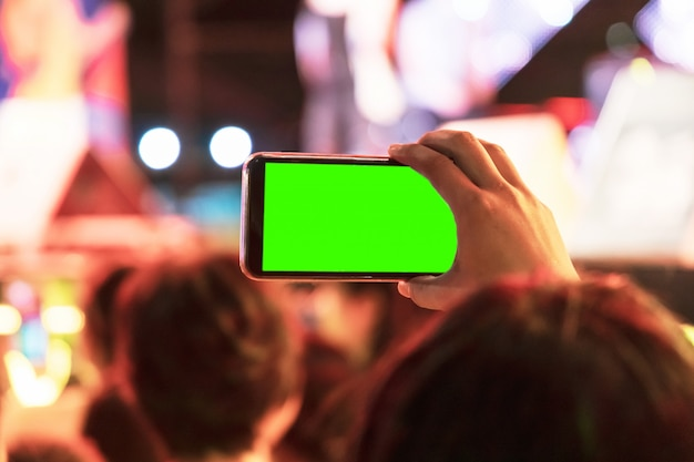 Hands of audience crowd people taking photo with mobile smart phone with green screen in party concert. Premium Photo