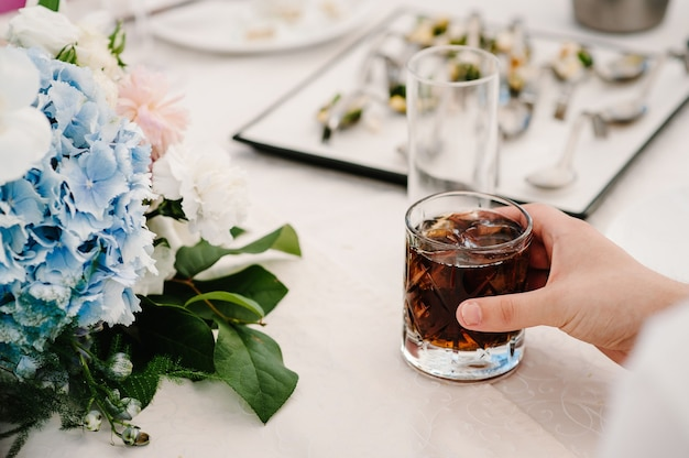 Hands of a bartender at bar, restaurant, man with glass whiskey. glass of scotch, whiskey with ice cubes on a rustic festive table, copy space  closeup, drinks. Premium Photo