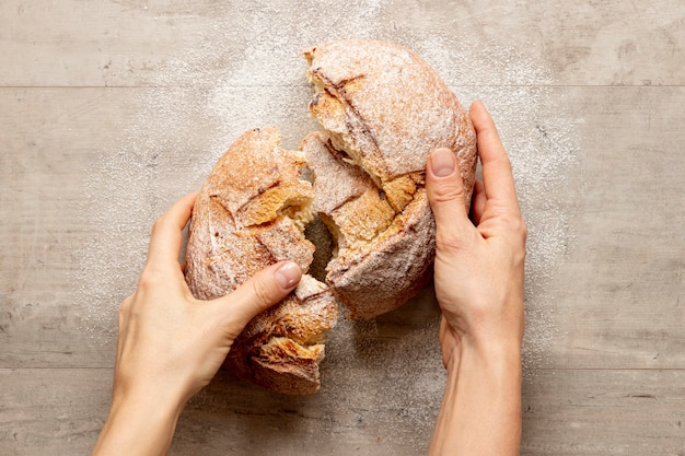 Hands breaking a delicious bread Free Photo