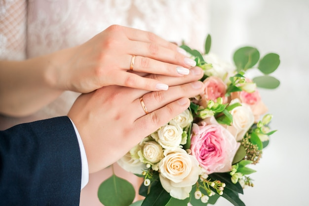 Hands of the bride and groom wearing white gold wedding rings on their hands Premium Photo