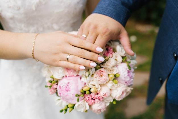 The hands of the bride and groom with wedding rings lie on the wedding bouquet of flowers Premium Ph