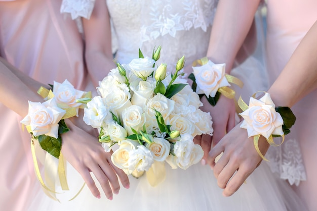 Hands of the bride and her bridesmaids with a bouquet Premium Photo