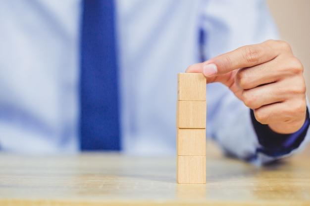 Hands of businessmen,stacking wooden blocks. Premium Photo