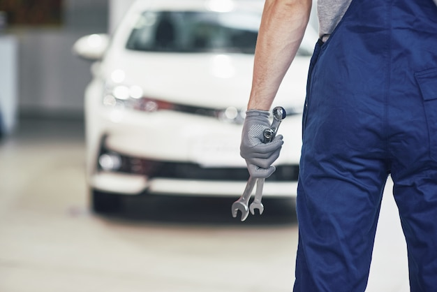 Hands of car mechanic with wrench in garage Free Photo