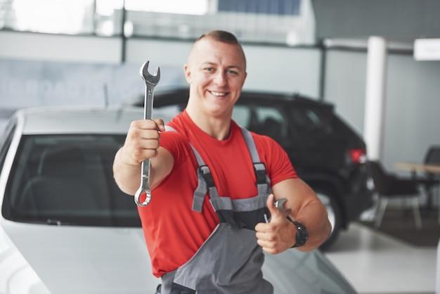 Mani del meccanico di auto con la chiave in garage. Foto Gratuite