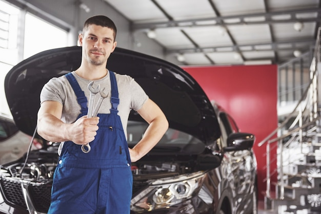 Hands of car mechanic with wrench in garage. Free Photo