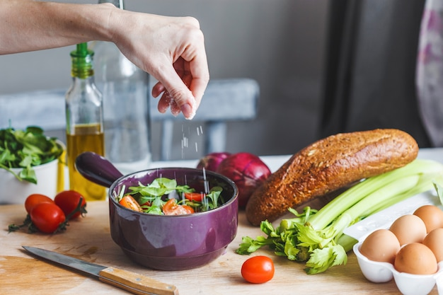 Hands of chefs prepare a salad of fresh and healthy ingredients, vegetables and olive oil in the kitchen Premium Photo