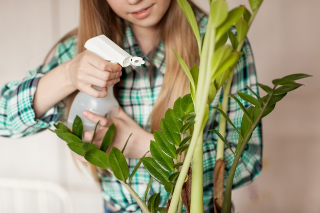 Hands of the child caring for plants at home, sprinkling the plant with clean water from a bottle. Premium Photo