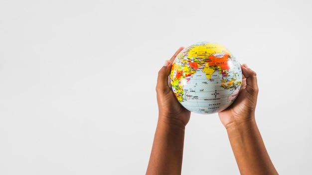 Hands of child with globe in studio Free Photo
