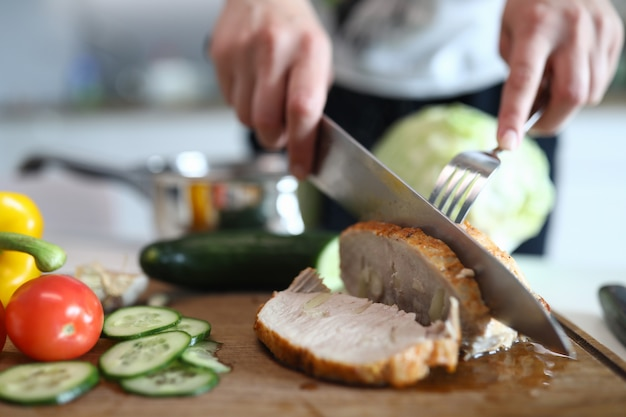 Hands chop ready baked pork meat and vegetables Premium Photo