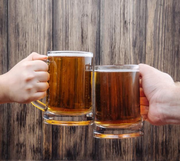 Руки чокая кружки пива на деревенский деревянный вид сбоку Бесплатные Фотографии