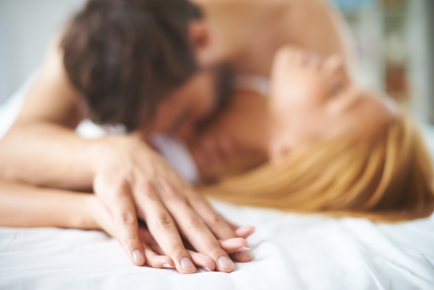 Hands close-up of a couple kissing in a bed  Free Photo