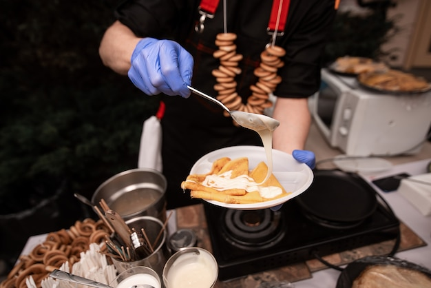 Hands cooks in blue gloves hold hold a plate of pancakes and impose a filling. pancake week Premium Photo