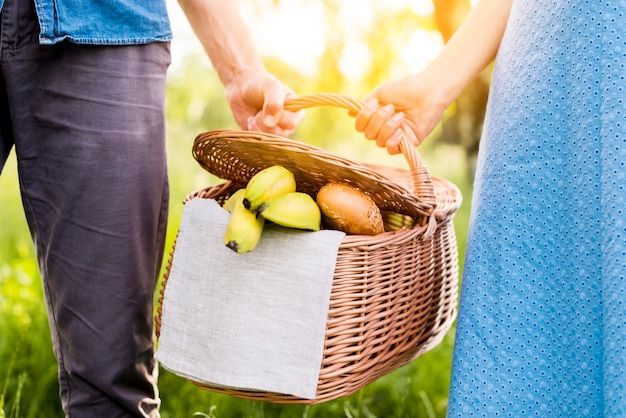 Hands of couple holding picnic basket full of food Free Photo