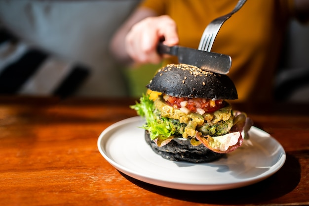 Hands cuts broccoli quinoa charcoal burger topped with guacamole, mango salsa and fresh salad by knife and fork. Premium Photo