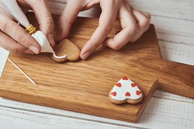 アイシングでジンジャーブレッドクッキーを飾る手 Premium写真