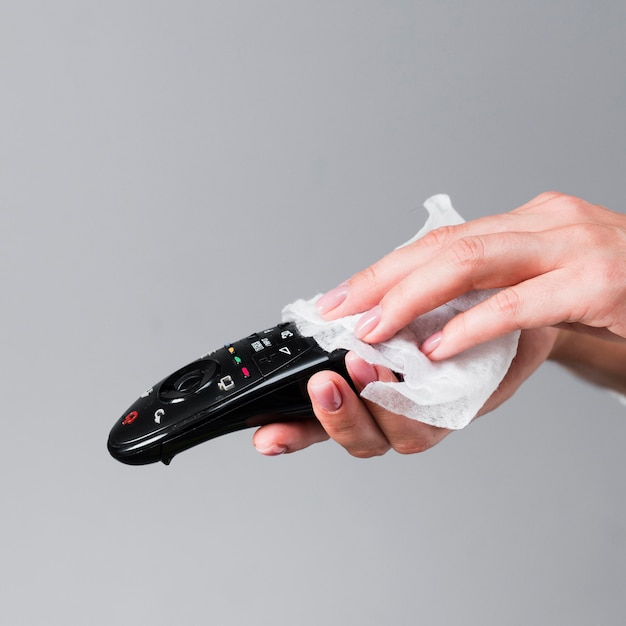 Hands disinfecting remote control Free Photo