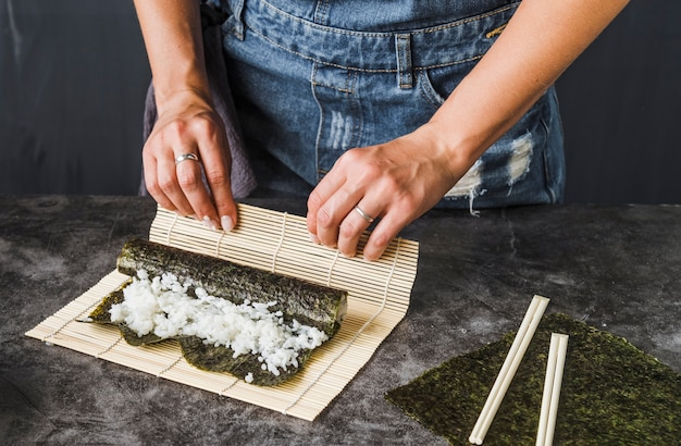 Hands doing wrap with sushi mat Free Photo