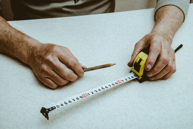 Hands of elderly working man with pencil and roulette close up. Premium Photo